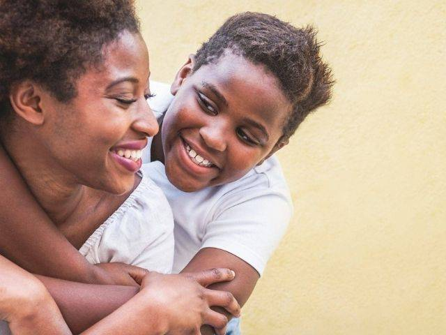 Adoption support is available to all of our families like this woman with teenage child hugging her from behind