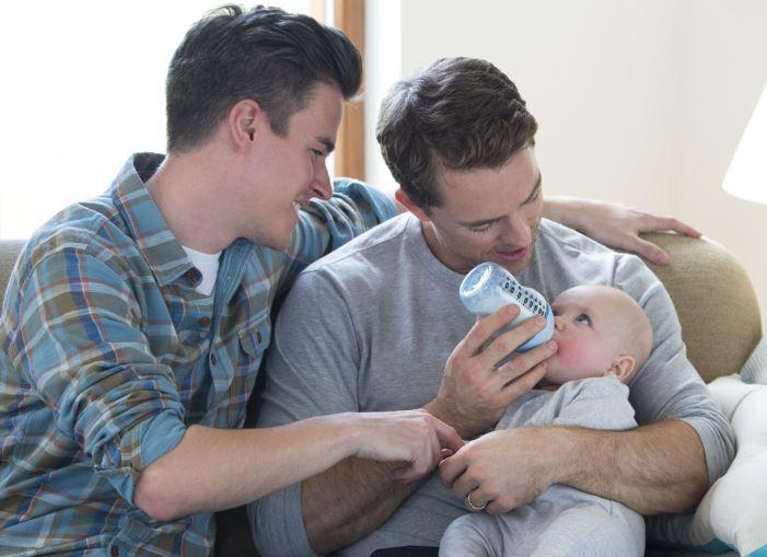 2 white men feeding bottle to baby