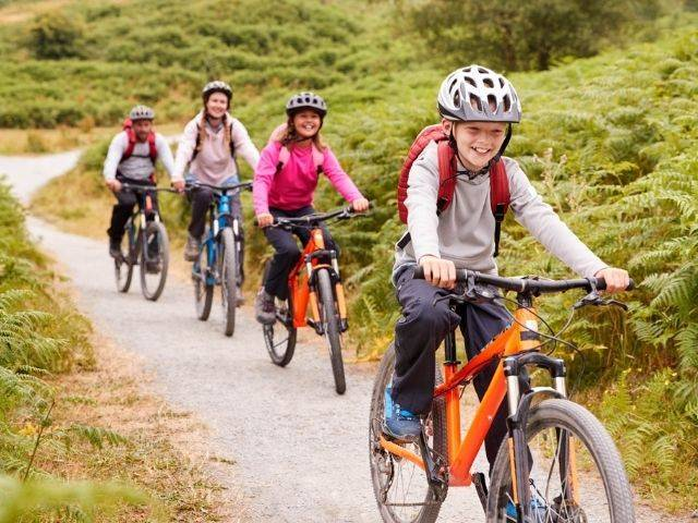 family out cycling on rural path