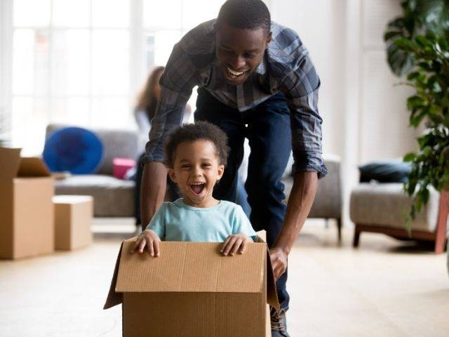 black man playing with child in cardboard box