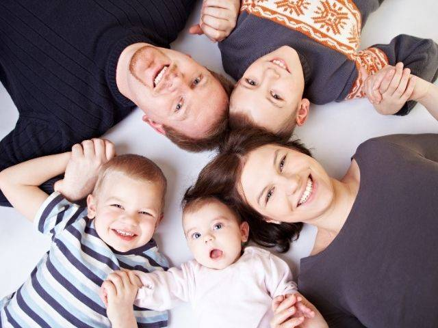 white family on floor looking upwards heads together