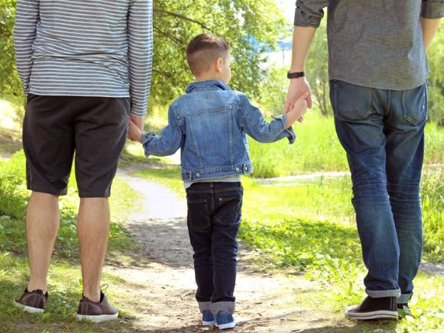 2 adults walking in the outdoors with child walking between them - holding hands