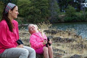 Mother and adopted daughter sitting by a river bird watching and laughing together