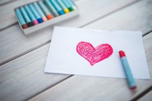 Pink heart drawn on white paper with a crayon