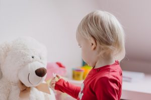 Toddler playing with teddy bear