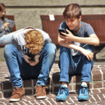 2 teenagers on their mobile phones