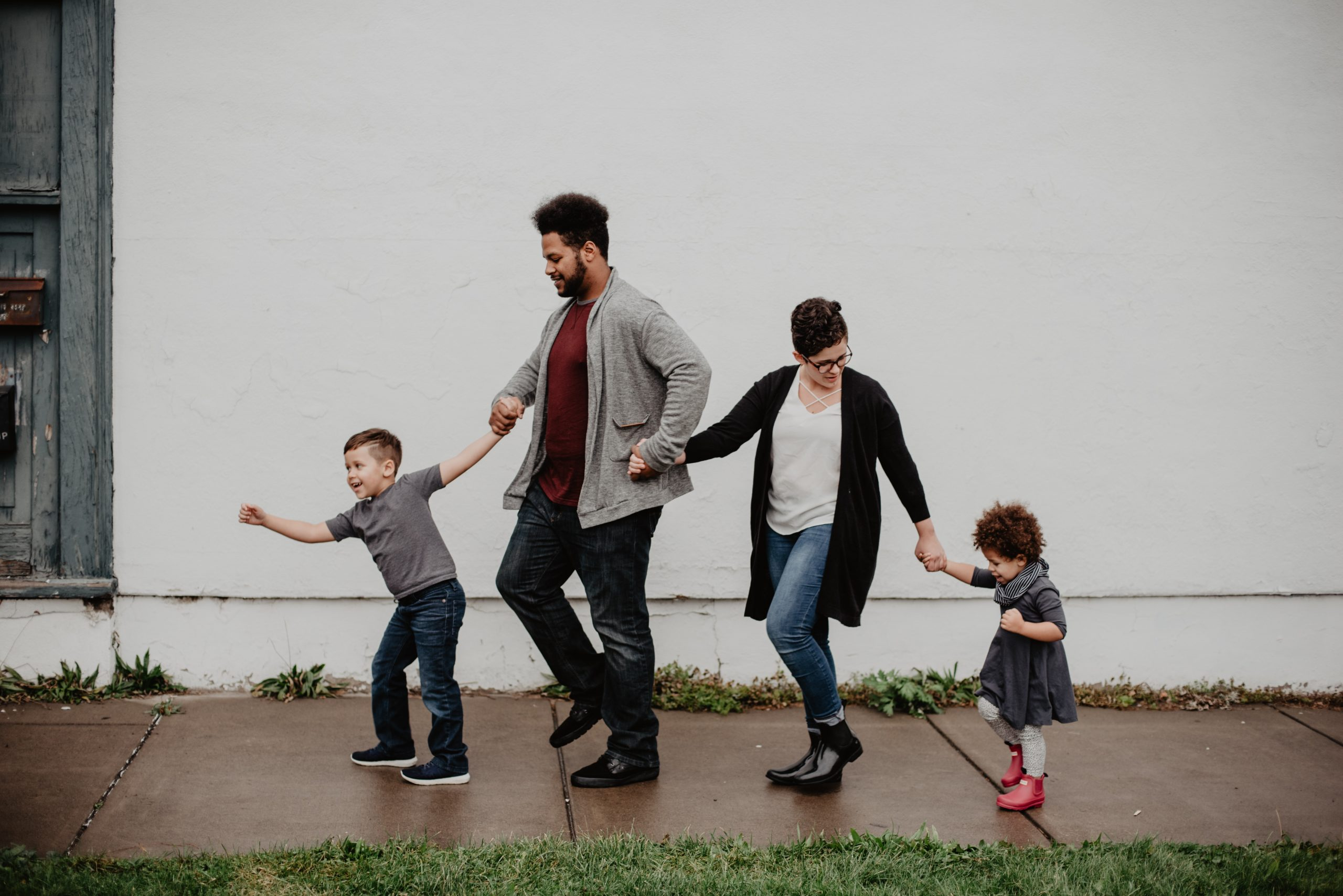 foster family consisting of a man and lady with 2 young children walking along a pavement in front of a white wall