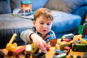 little boy playing at table in front of sofa with toys
