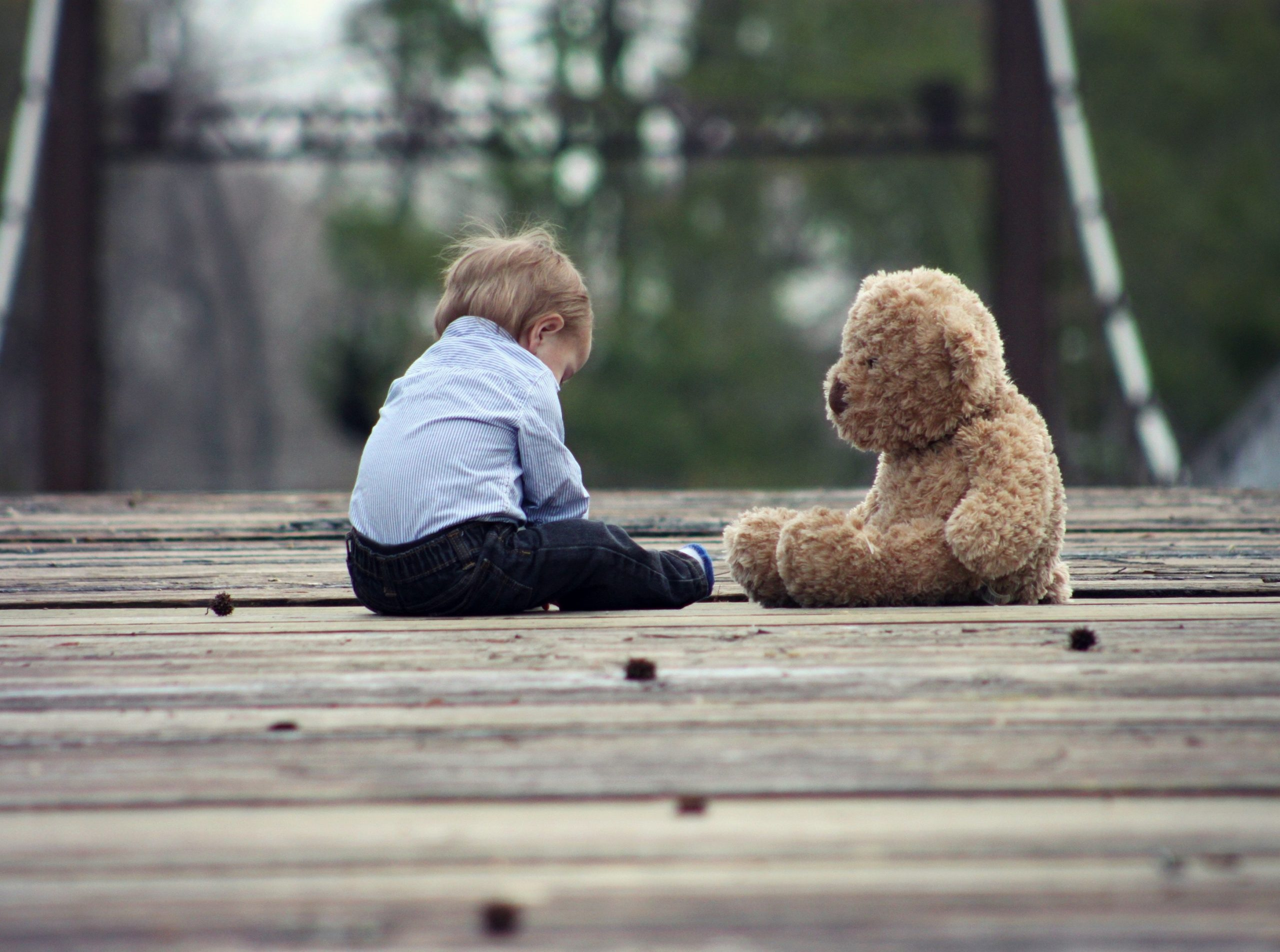 Back view of a young child affected by trauma sitting on decking with giant teddy bear.